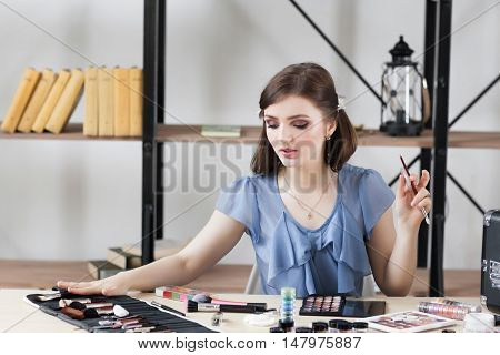 Professional visagiste choosing brush for makeup. Artist tells about importance of each tool for visage making. Beauty, fashion, cosmetics concept