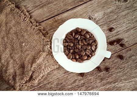 Coffee cup with burlap and roasted coffee beans. Top view image.