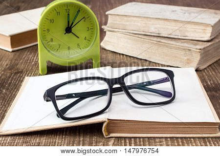Books with glasses and alarm clock on the desk