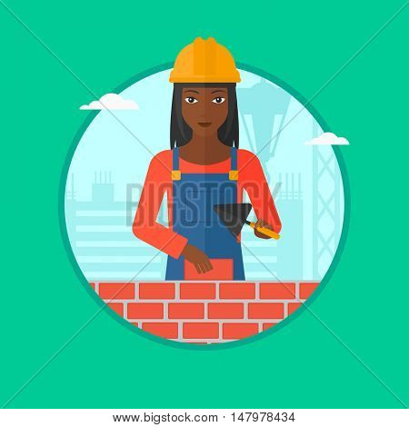 African-american bricklayer in uniform and hard hat. Bricklayer working with a spatula and a brick in hands on construction site. Vector flat design illustration in the circle isolated on background.