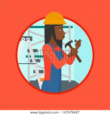 An african-american female worker hammering a nail into the wall. Worker in overalls and hard hat nailing with hammer in apartment. Vector flat design illustration in the circle isolated on background