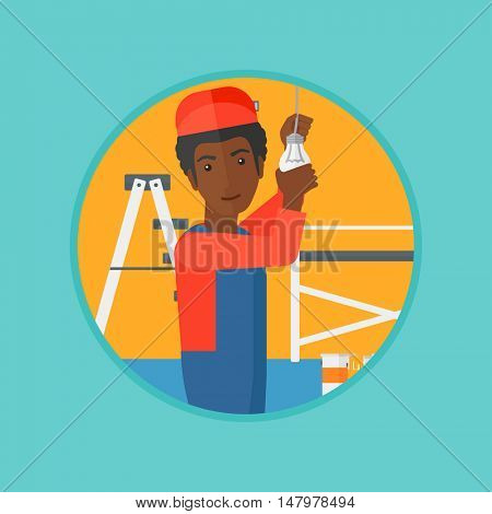 An african-american electrician twisting a light bulb. An electrician installing light in an apartment. Man changing light bulb. Vector flat design illustration in the circle isolated on background.