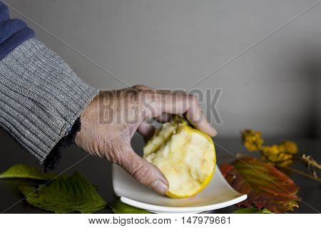 Female hand holding a bitten apple laid on the saucer, studio closeup shot with a shallow depth of field