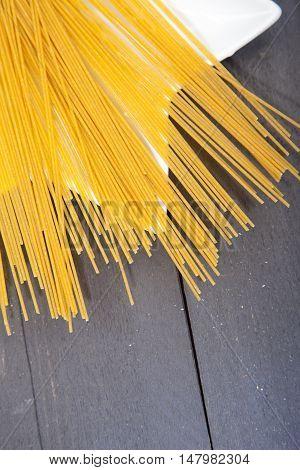 Pile of spelt spaghetti on white platen on wooden table