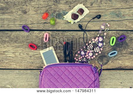 Children's handbag and accessories: mobile phone, hair bands, candy, beads, headphones on old wooden background. Top view. Toned image.