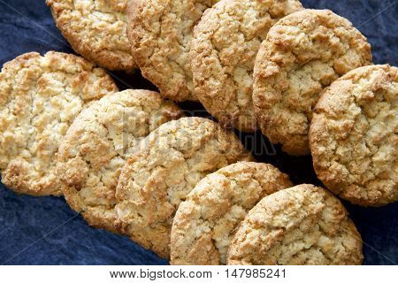 Homemade Anzac biscuits on a dark slate background.