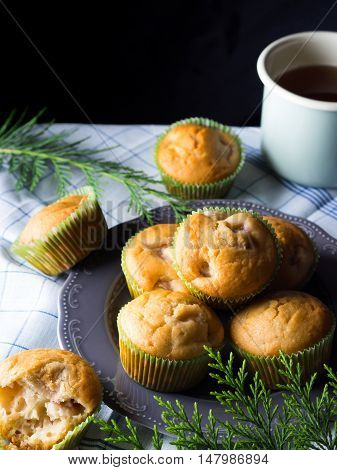 Vegan eggs free spelt wheat muffins with peaches and apples in green paper cases on checkered napkin. Vertical image