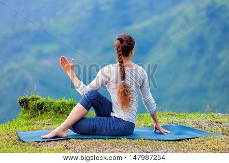 Hatha yoga outdoors - sporty fit woman doing yoga asana Parivrtta Marichyasana (or ardha matsyendrasana) -  seated spinal twist outdoors in mountains