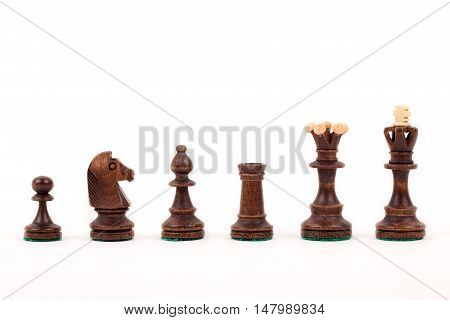 Brown wooden chess pieces on a white background