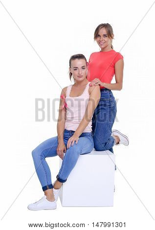 voluntary two young women posing on white background and wearing pink for breast cancer