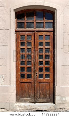 Old wooden door with glass windows many layers of brown varnish