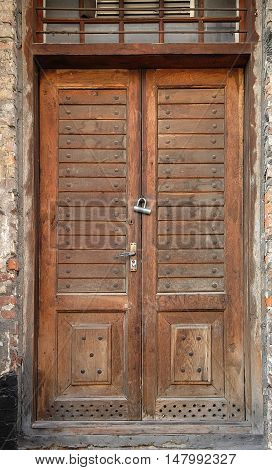 Old wooden door with wrought iron rivets lock