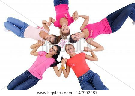 Group of young women lying on white background and hand in hand, a pink breast cancer awareness ribbon breast checks.