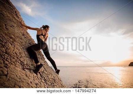 Female extreme climber conquers steep rock against the sunset over the river.