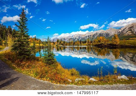 The concept of hiking. Path around the lake. Canmore, near Banff National Park. Mountains and scenic cumulus clouds are reflected in the water