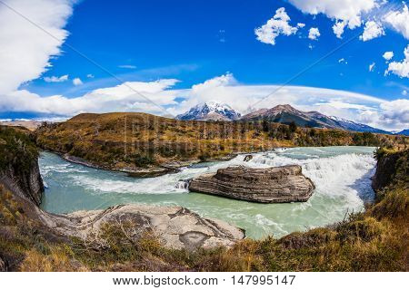 Patagonia, Torres del Paine National Park - Biosphere Reserve. Chile, Cascades Paine. Cold emerald water of the river Paine with a roar there pass rocky barriers