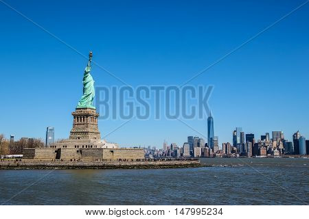 Statue of Liberty on a sunny day Manhattan in the background.