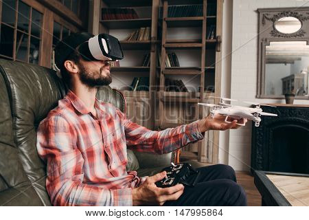 Man in vr glasses launching drone indoors. Young male controls quadrocopter using virtual reality headset and remote control