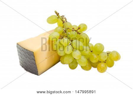 Piece of a hard cheese and cluster of a white table grapes on a light background
