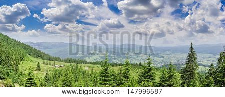 Panorama of the Carpathian Mountains with spruces and the mountain pasture with outbuildings in the foreground against a background of ridges valley with mountain village and the sky with clouds