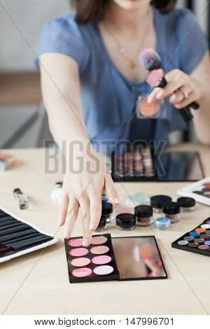 Artist taking rouge with brush, visagiste workplace. Close-up of stylist hand on palette with pink shades bluster. Beauty, makeup, cosmetics concept