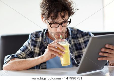 leisure, technology, communication and people concept - creative man with tablet pc computer and earphones listening to music and drinking shake at cafe table
