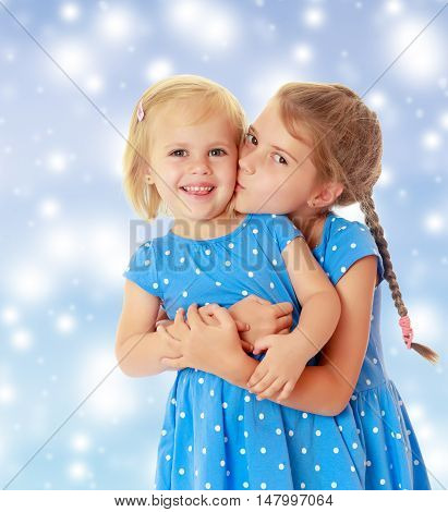 Two charming little girls, sisters , in identical blue dresses with polka dots. Older sister kissing the younger on the cheek.On a blue background with large, white,