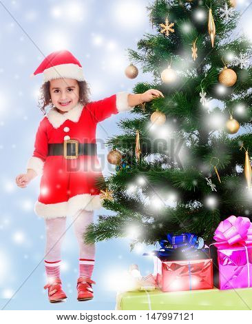 Smiling curly-haired little girl, dressed as Santa Claus decorates a Christmas tree toys.Blue winter background with white snowflakes.