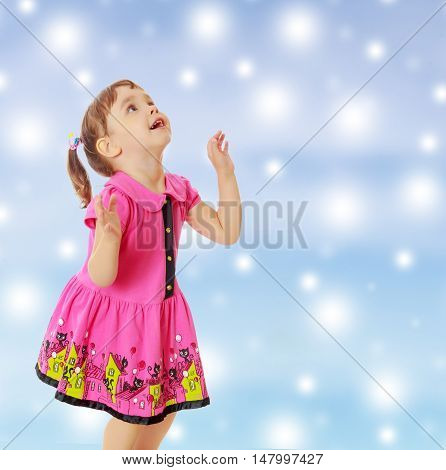 Pensive little girl with pigtails on the head , in a pink dress. The girl was looking at the top turned sideways to the camera.On new year or Christmas blue background with white big stars.