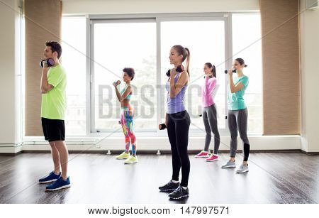 fitness, sport, training and exercising concept - group of smiling people working out with dumbbells flexing muscles in gym