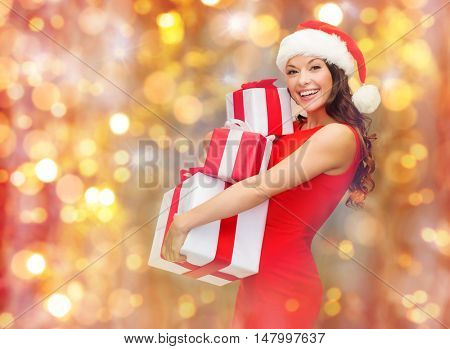 christmas, holidays, celebration and people concept - happy smiling woman in santa hat and red dress holding gift boxes over lights background