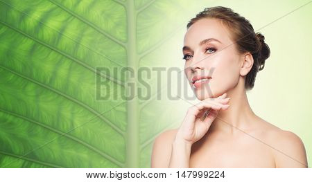beauty, people and health concept - beautiful young woman touching her face over natural green leaf background