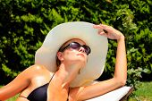 stock photo of sunbathing woman  - Beautiful young woman at a pool - JPG