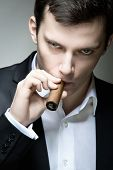 stock photo of cheater  - A young man looking suspicious with a cigar - JPG