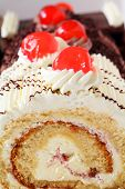 picture of sponge-cake  - Slices of rolled sponge cake in vanilla and chocolate topped with glace cherries - JPG