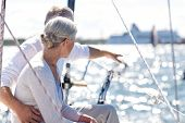 sailing, age, tourism, travel and people concept - happy senior couple pointing finger on sail boat  poster