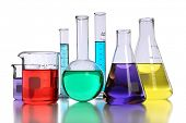 stock photo of flask  - Laboratory glassware with various colored liquids with reflection on table - JPG