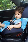 Постер, плакат: малыш мальчик сидит в сиденье автомобиля