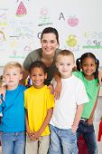 stock photo of student teacher  - group of preschool kids and teacher in classroom - JPG