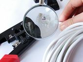 Hands Cheking The Network Cable (Cat5E) Under A Magnifier& Crimper Is Under It. poster