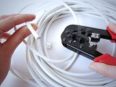 Hands Using Network Cable (Cat5E) Crimper poster