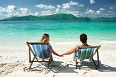 stock photo of beach holiday  - Couple on a tropical beach in chaise lounge - JPG