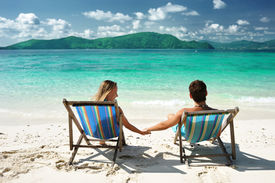 image of beach holiday  - Couple on a tropical beach in chaise lounge - JPG