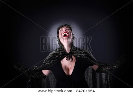 A portrait of a hooded female vampire standing against black background
