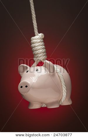 Piggy Bank Hanging in Hangman's Noose on Red Spot Lit Background.
