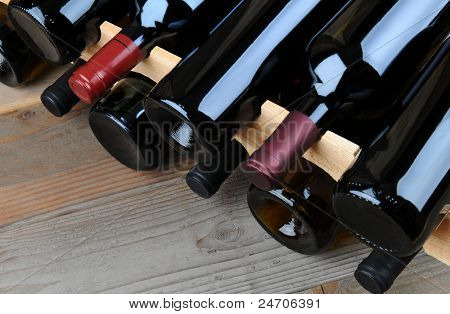 Closeup of a wine rack full of bottles on a rustic wooden table.