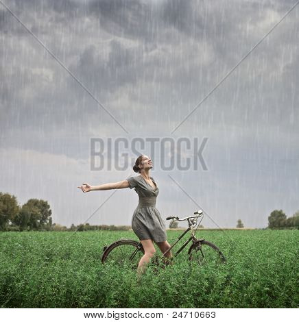 Beautiful woman cycling on a green meadow in the rain