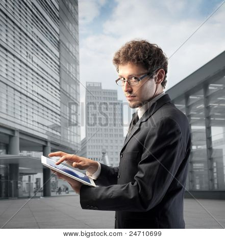 Businessman using a tablet pc with office buildings in the background