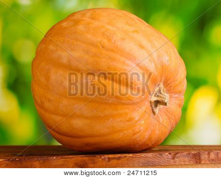 pumpkin on wooden table on green background