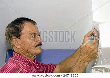 Senior Man With Screwdriver And Screw